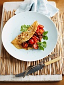 A pancake with cherry tomatoes and peppers