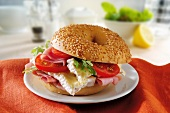 A sesame seed bagel with brie, ham and tomatoes