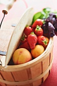 Apricots and strawberries in a wooden basket