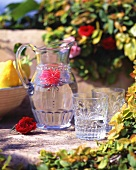 Jug of water with flower and water glasses