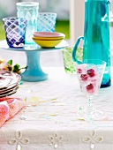 Glass with raspberry ice cubes on a table set for summer