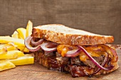 Steak sandwich with cheddar, onions and BBQ sauce