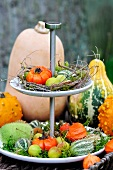 An autumnal cake stand with pumpkins, moss and crab apples