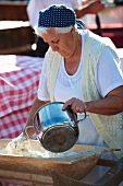 An elderly woman making bread dough in a kneading trough (Hungary)