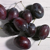 Several plums on a white wood surface