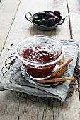 Homemade plum compote with cinnamon sticks