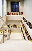 Ausgestellte Keramikbehälter und Figuren auf gemauerten Ablagen im Treppenhaus