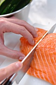 A salmon fillet being cut into portions
