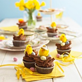 Chocolate cupcakes on a table decorated for Easter