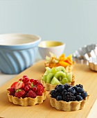 Various fruit tartlets on a chopping board