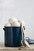 White chicken's eggs in an enamel pot