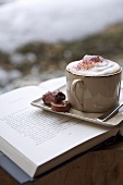 A cappuccino with pralines on a saucer sitting on a open book
