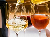 White wine being poured into a glass next to a glass of rose and red wine