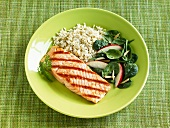 Grilled Salmon with Rice and Spinach Salad with Sliced Radish and Almonds; On a Green Plate