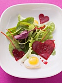 Mixed leaf salad with a beetroot heart and a fried egg