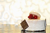 A white cream cake topped with berries and a macaroon