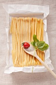 Tagliatelle and a tomato, salt and basil on a wooden spoon