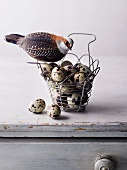 A decorative bird perched on a wire basket of quail's eggs