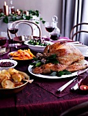 Roast turkey and side dishes of a table laid for Christmas dinner