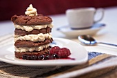 A tower of chocolate biscuits with mascarpone-marsala cream on berry sauce