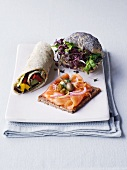 A wrap, a slice of wholemeal bread topped with salmon and a poppy seed roll filled with cress