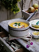 Pumpkin soup in a pot on a rustic table