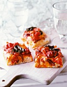 Slices of pizza topped with onions and tomatoes