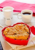 A heart-shaped apple cake with raisins and a cup of coffee