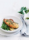 Breaded chicken breast with herb butter and green beans