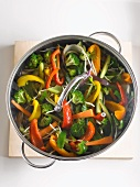 Sautéed vegetables in a pot with a glass lid (seen from above)
