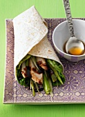 A wrap filled with chicken, spring onions and soy sauce