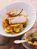 Chicken breast fillet with a cornflake coating on a carrot medley with pistachios and coriander