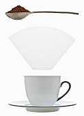 A coffee cup, filter paper and a measuring spoon of ground coffee