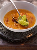 Spicy tomato and carrot soup with yogurt and pistachio dumplings
