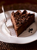A slice of chocolate tart with chocolate curls