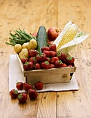 Strawberries, corn cobs, vegetables and apples in a wooden basket
