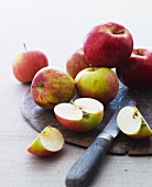Apples on a board, chopped and whole