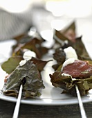 Meat kebabs wrapped in vine leaves with a yogurt dip