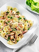 Bow Tie Pasta with Peas, Ham and Mushrooms in a White Dish; Fork