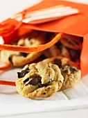 Chocolate chip cookies falling out of a bag