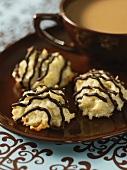Coconut macaroons decorated with chocolate stripes and a cup of coffee