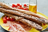 Bread sticks, raw ham and cherry tomatoes