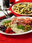 An anti-pasti platter and penne with pancetta and leafy vegetables (Italy)
