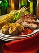 A grill platter with spare ribs, baked potatoes with Cheddar cheese and corn cobs