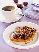 Damson cake with chopped almonds on a plate with a cup of coffee