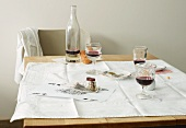 Red wine, bread, salt and pepper on a table after a meal
