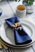 A place setting with a blue napkin and a napkin ring made of shells