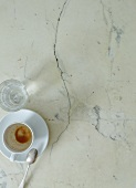 An empty coffee cup and a water glass on a marble table