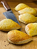 Mini cheese and onion pasties on a wooden board