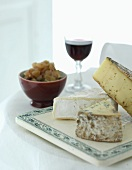 A cheese platter with chutney and red wine